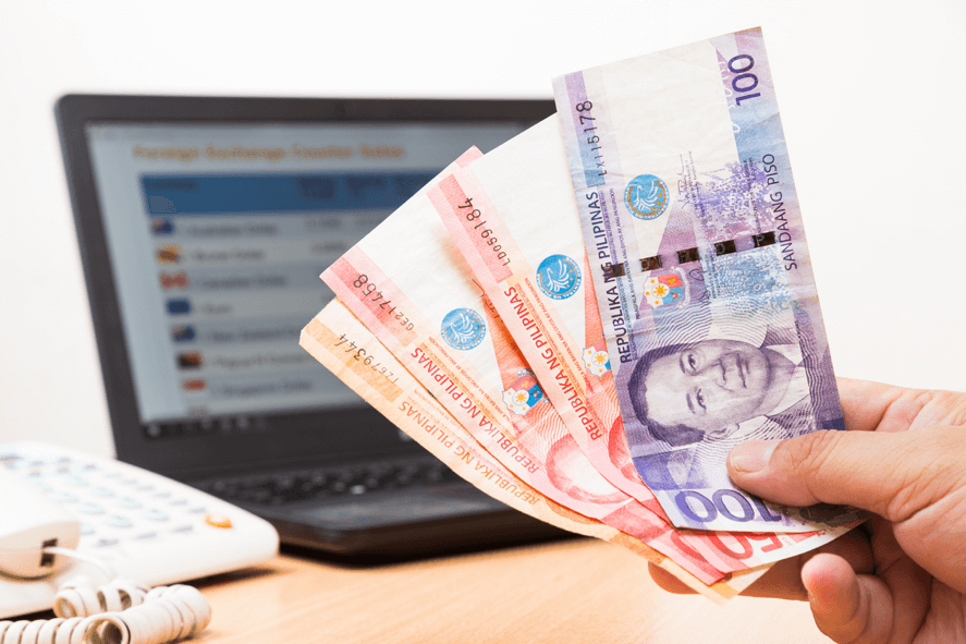 Hand holding Philippine peso bills with laptop and telephone in the background.