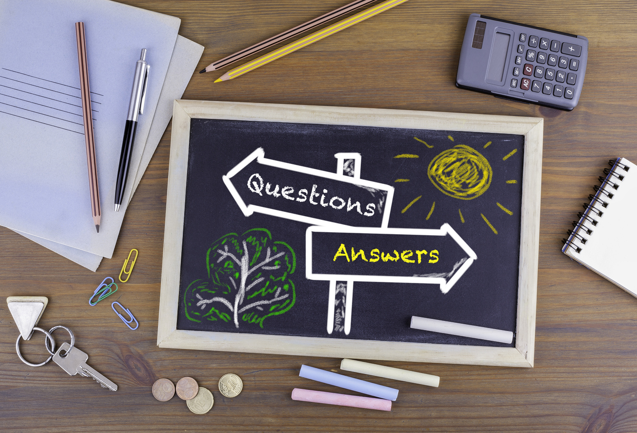 Questions Answers signpost drawn on a blackboard.