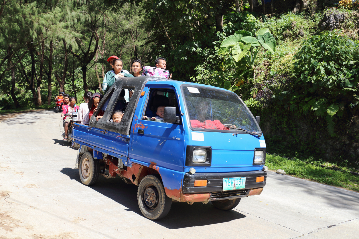 Several people riding a small blue truck in the mountains.