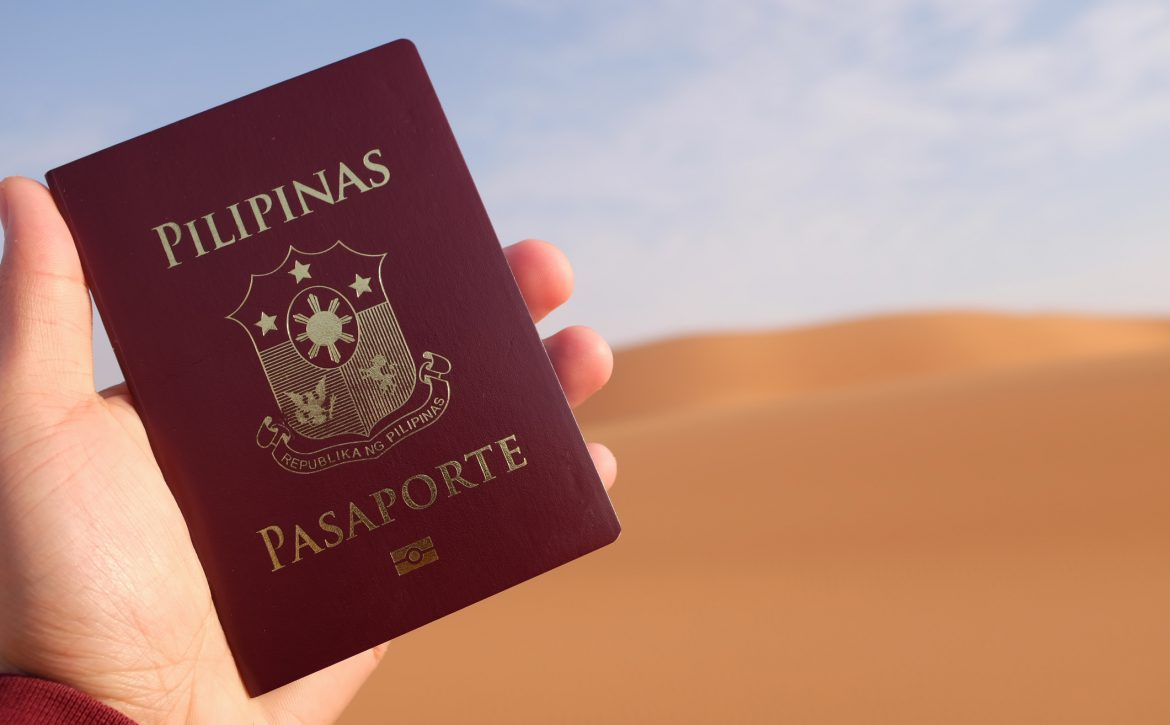 Hand holding up a Philippine passport in a desert.