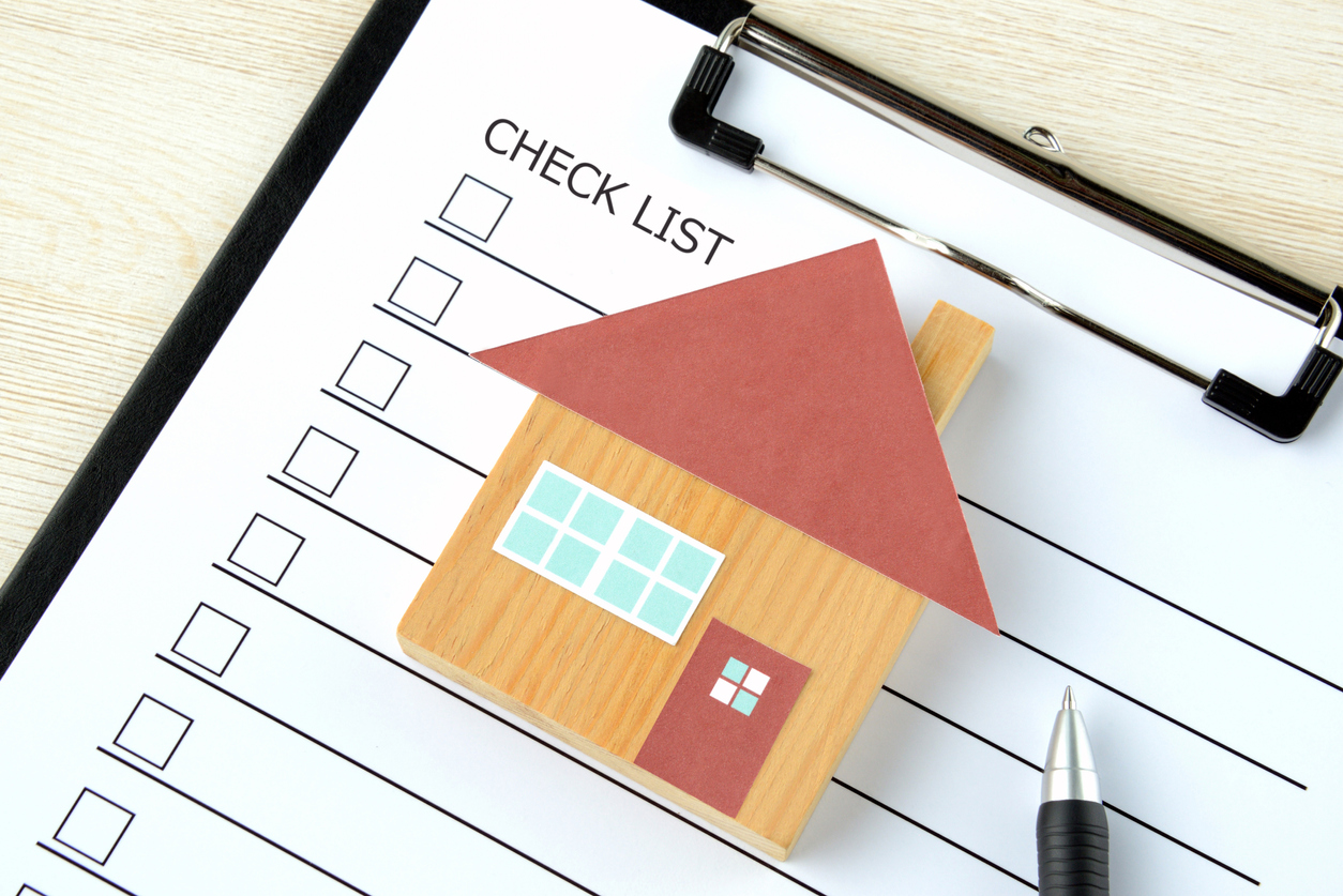 A printed checklist document with a small house figure made of wood placed on top.