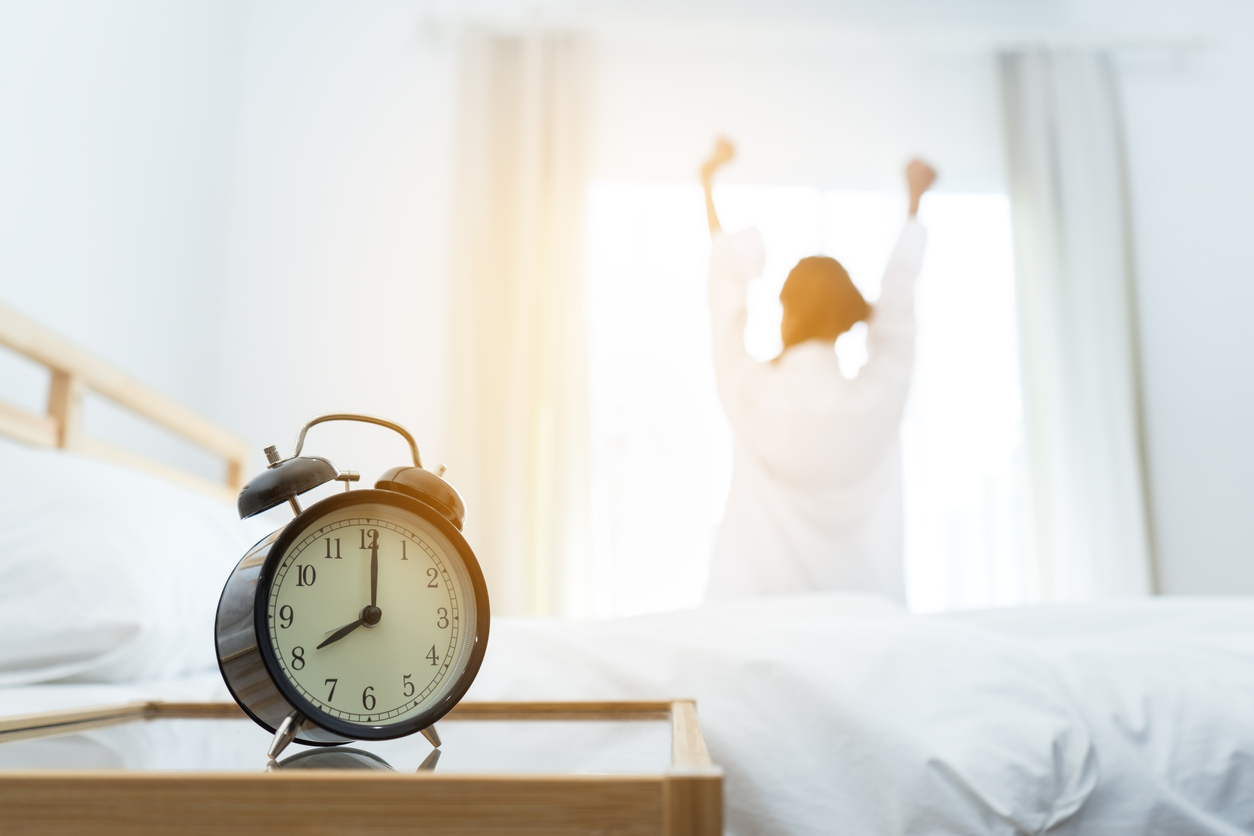 Alarm clock set at 8AM and girl stretching with her arms up in the background.