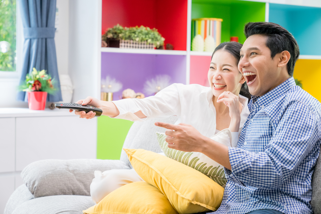 An excited couple happily watching TV.