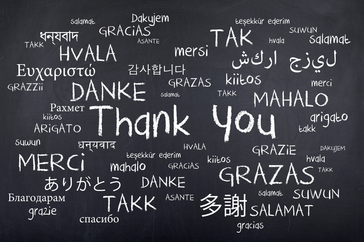 Different translations of thank you handwritten on a black board