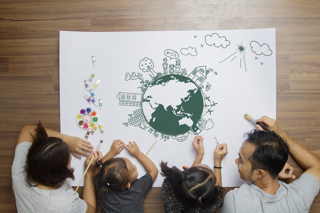 A whole family with mom, dad and two daughters all drawing on a big canvas together.