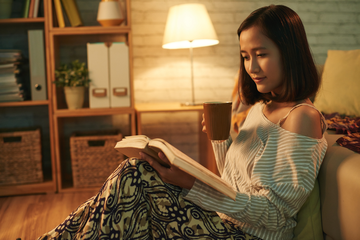 A girl sat on a couch while reading a book.