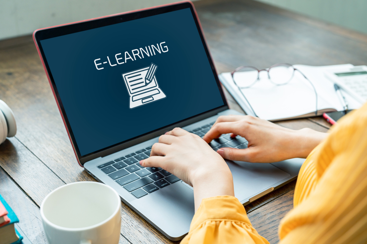 A lady's hands typing on a laptop with screen showing e-learning
