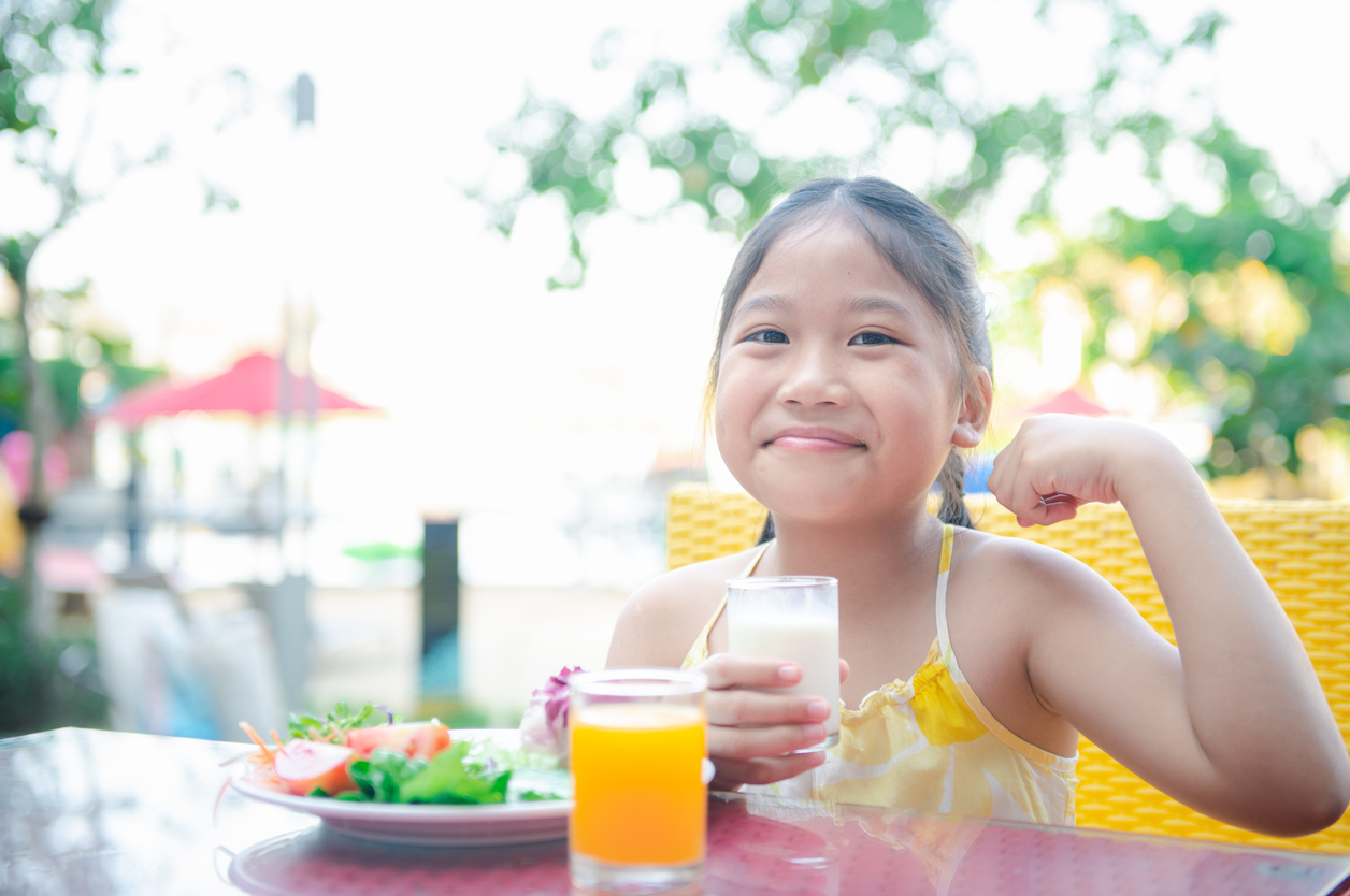Girl eating healthy food and proudly holding a glass of milk