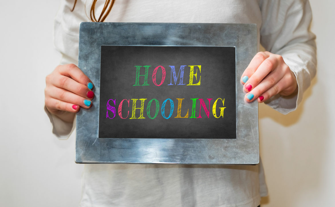 "Girl holding up a small blackboard with colourful writing of ""Home Schooling"""