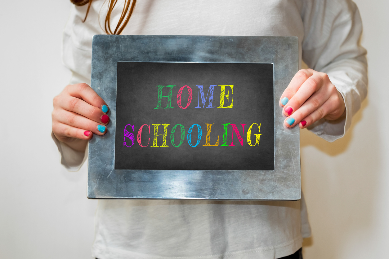 """Girl holding up a small blackboard with colourful writing of """"Home Schooling"""""""